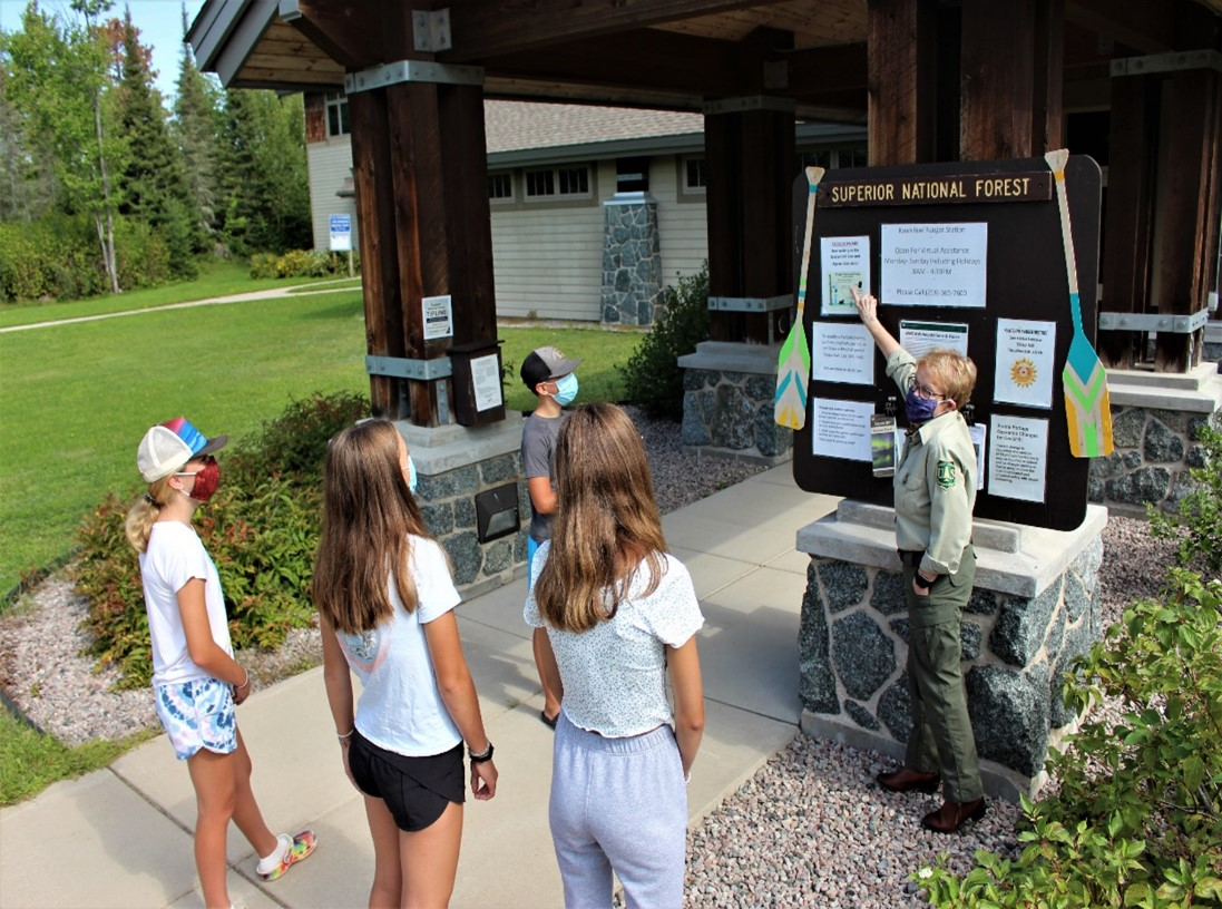 Visitor Information and Services Ranger Maggie Whiting directs a group of young