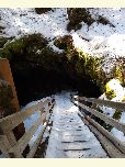 Snow covered staircase leads down into a darkened cave.