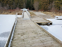 Photo showing a weatherered wooden dock on a frozen lake.