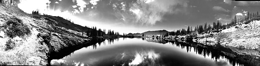 Panoramic view of lake and mountains in black and white
