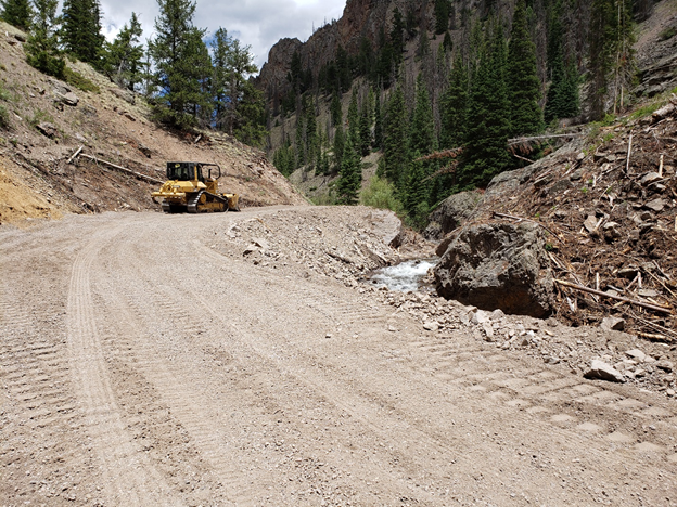 dirt road repaired with bulldozer in background smoothing out road surface