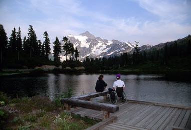 Graphic for the program with 2 people, one in a wheelchair, on a dock at a lake.