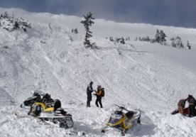 photo - Grand County  Search and Rescue handling an avalanche with snowmobiliers.