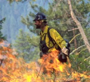photo of a man in fire clothing. In the foreground are flames.