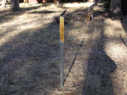 photo:  The photo shows a yellow, rectangular National Forest property boundary sign on a metal pos