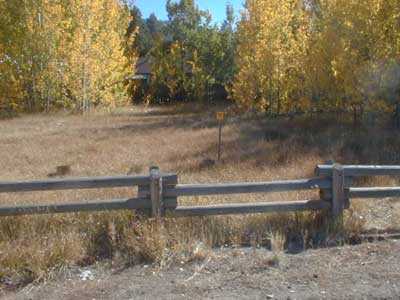 [Photo]: Photo of an Urban lot acquired under the Santini-Burton Purchase Authority. There is a wooden pole fence in the foreground and Aspen trees with yellow leaves in the distance. In the background is a neighboring house.