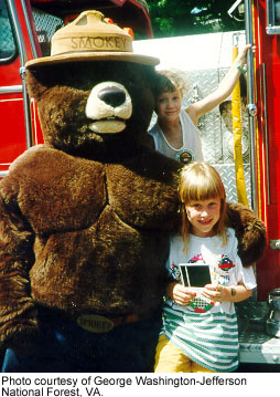 Smokey Bear with a child in front of a fire engine