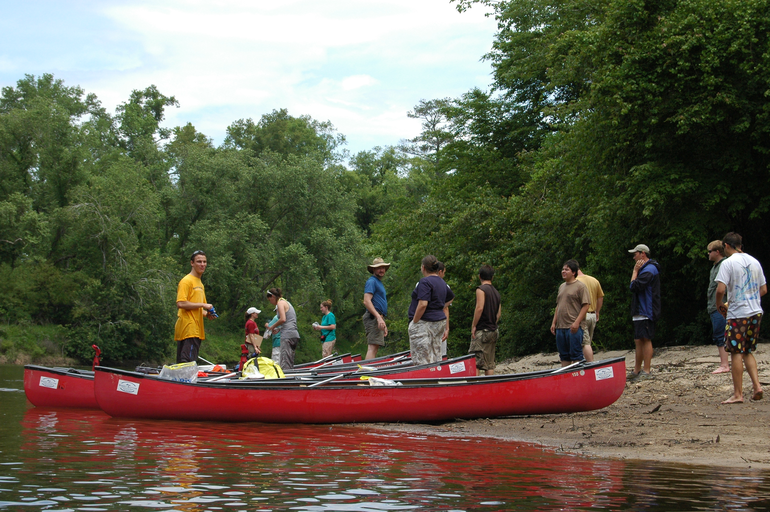 Photograph of volunteers cleaning up trash from river using canoes