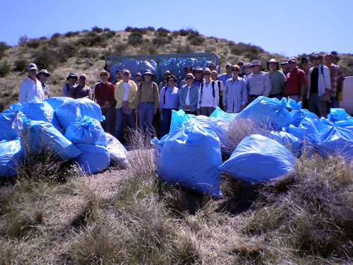 Group picture of volunteers and their bags full of weeds