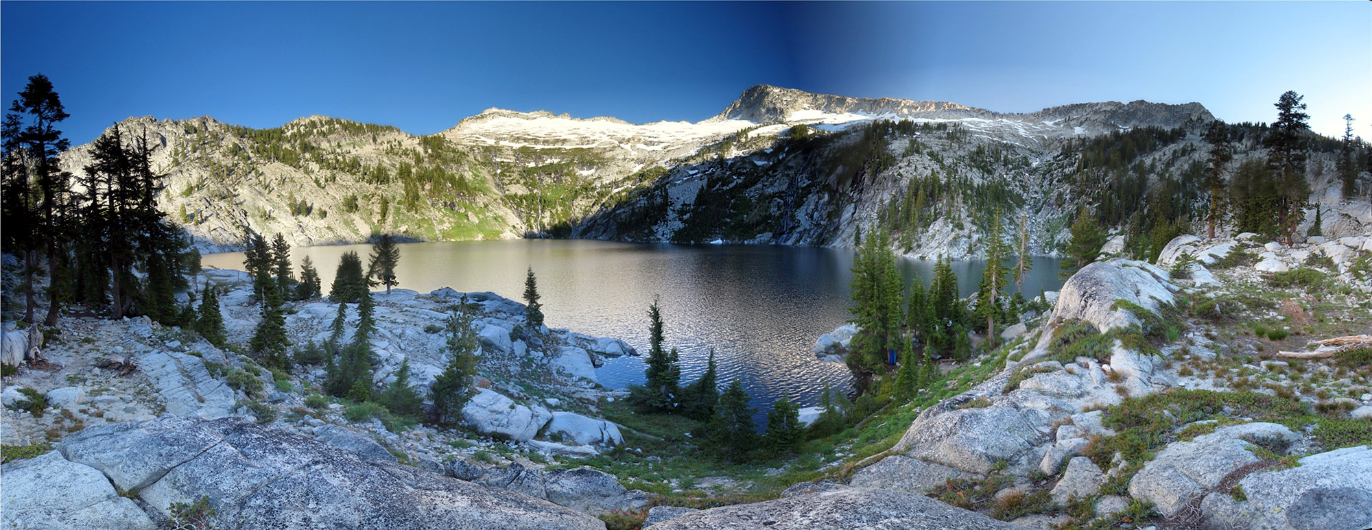 Wilderness lake with rocky sparsely forested hills all around it