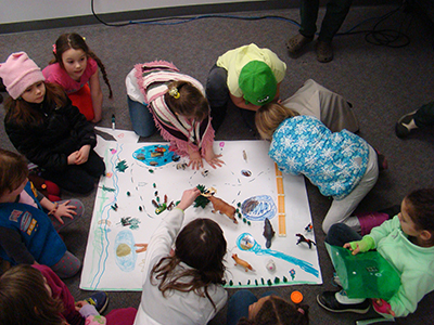 Girl Scouts drawing their concept of a Wilderness on recycled paper.