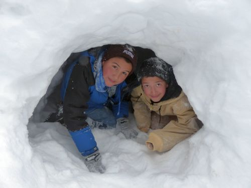 Photo of 2 young boys in a snow cave