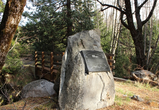 Trailside view of rock monument with plaque inset next to wooden footbridge