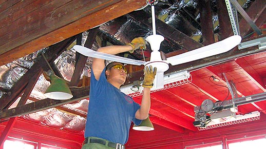 A man on a ladder uses tools to attach fan to ceiling.