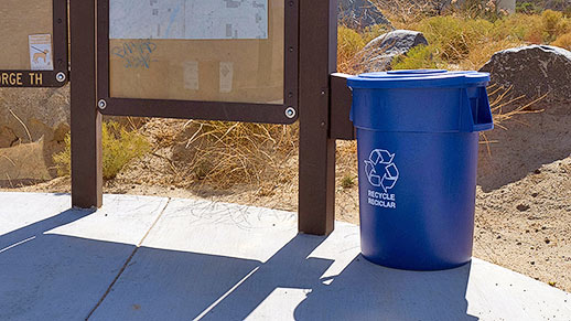 Plastic recyling can placed outdoors adjacent to signs.