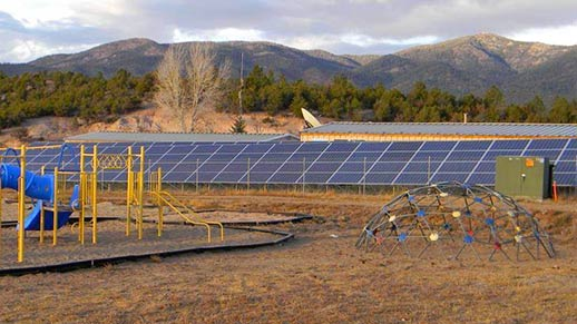 Solar panels on the ground next to a playground.