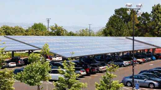 Photo of a parking lot with photovoltaic canopies with cars parked underneath.