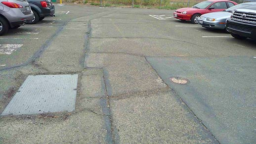 A photo of the failed paving in the existing RO parking lot.