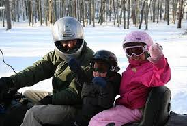 Adult and child riding a snowmobile