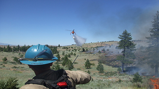 A helicopter drops water over a wildfire at one of the Tallac Hotshots watches.