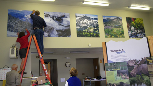 Photo of people hanging posters in the visitor center.