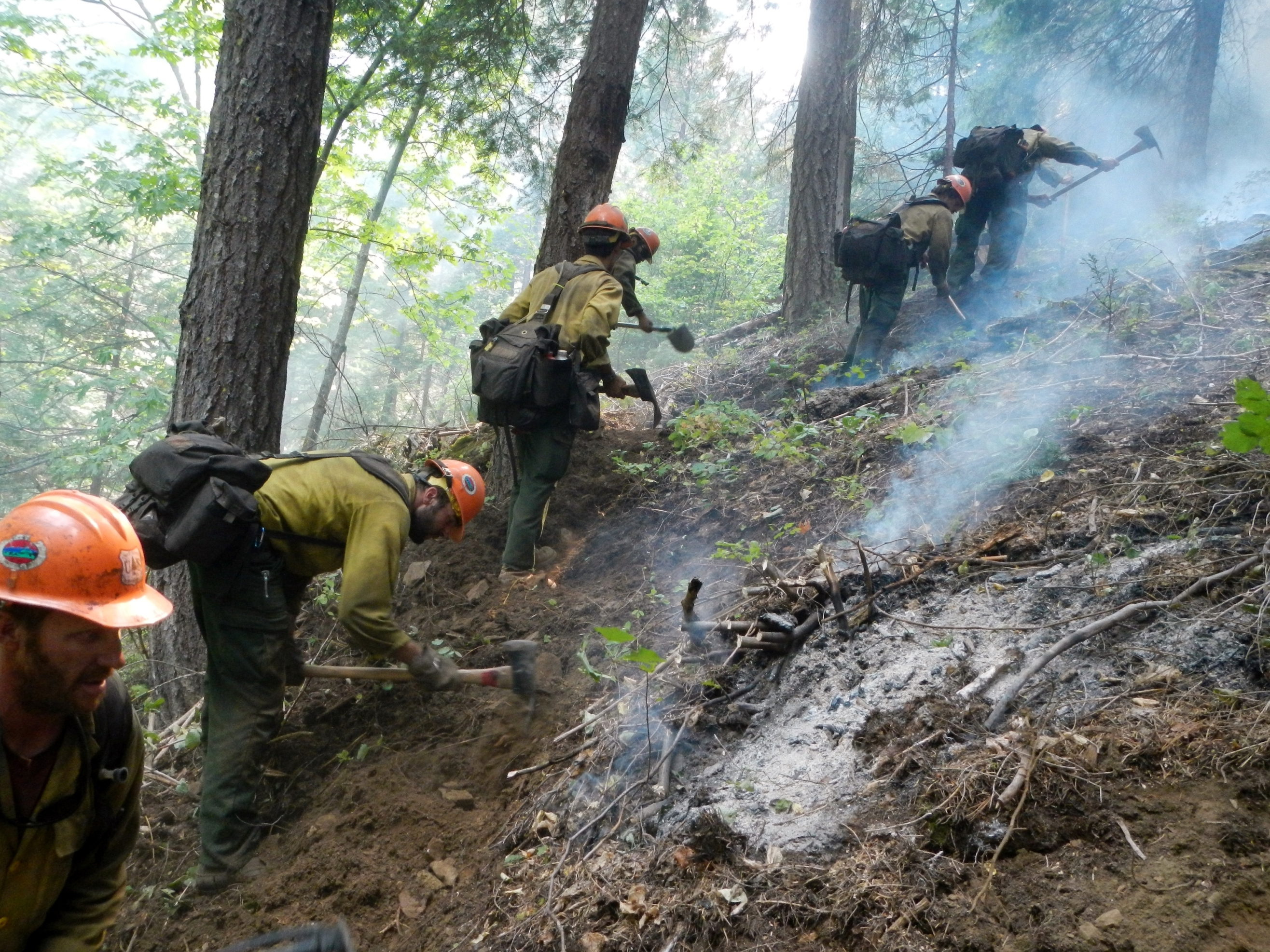 Five firefighters with hand tools dig line up a smoldering steep mountainside.