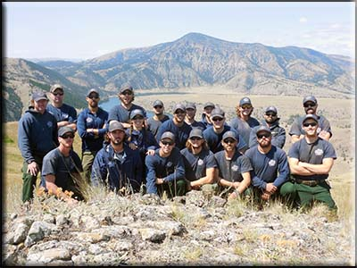 2013 Prescott Hotshots group photo wearing fire fighting uniforms with a mountainous background