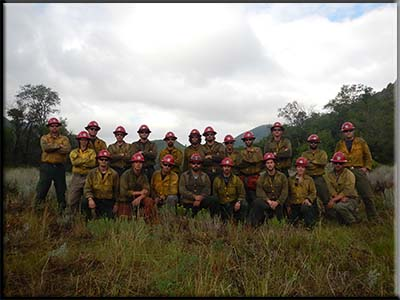 2014 Prescott Hotshots group photo in a forested setting wearing fire fighting uniforms