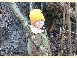 A child sports a blaze orange hat for safe hiking in autumn woods