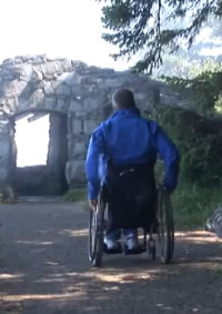 photo of man in wheelchair approaching stone arch on Whispering Spruce Trail