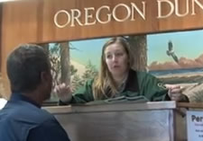 Forest Service staff giving information to visitor at the Oregon Dunes Visitor Center