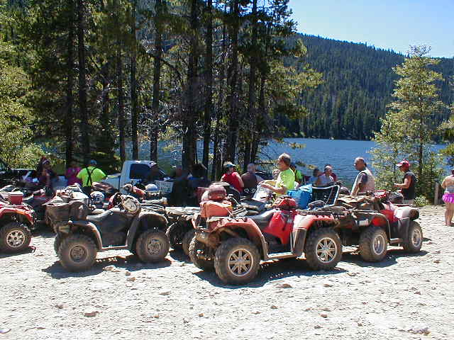 Several OHV riders off of a forest road on a clear, sunny day.