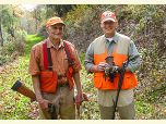 Two smiling old hunters wearing orange vests and hats with shotguns, their dog, and a ruffed grouse.