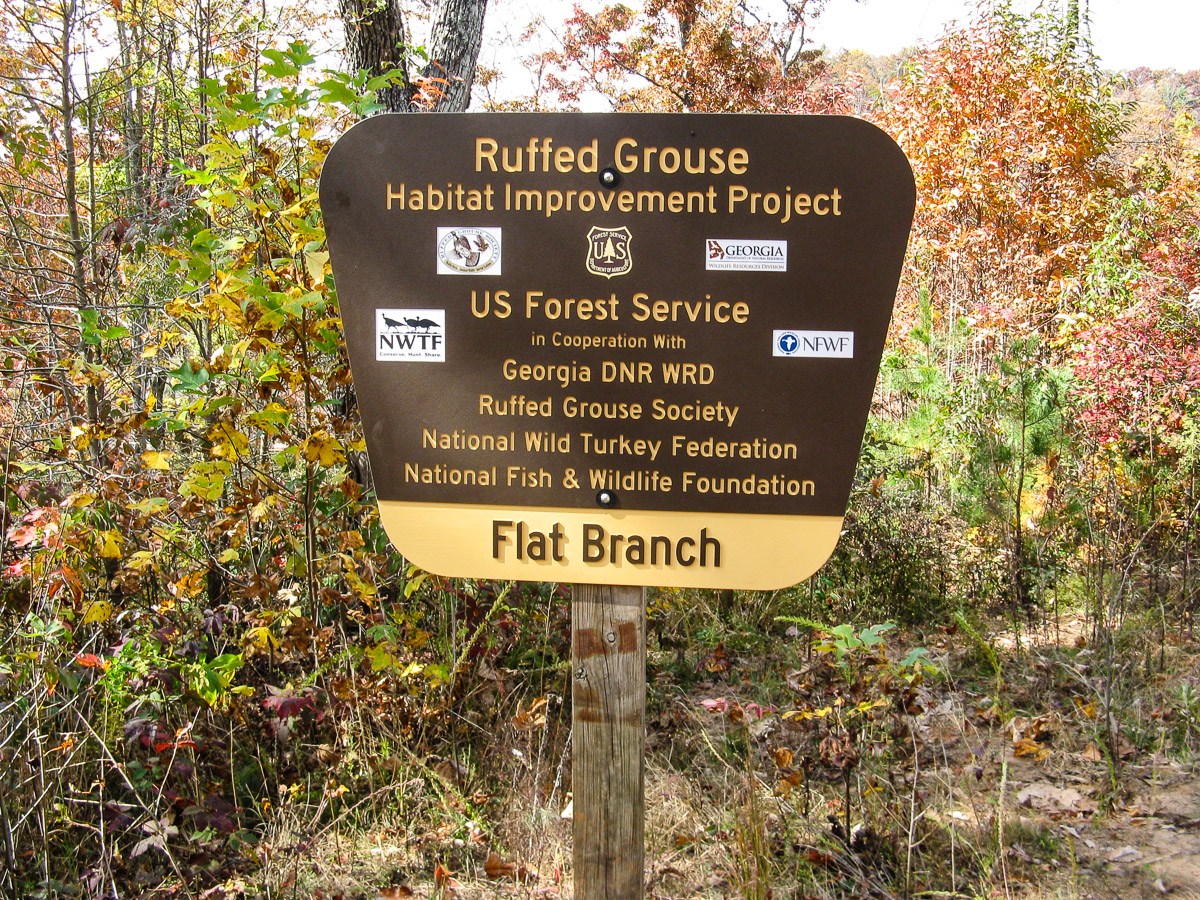 Brown and yellow sign shows partners in the Flat Branch Habitat Improvement Project