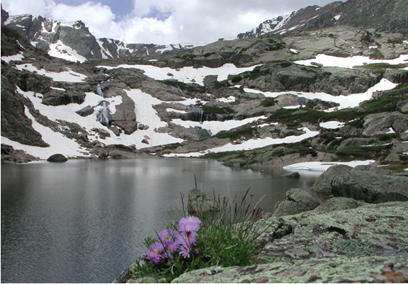 Large alpine lake with snowy patches on rocky mountain peaks.