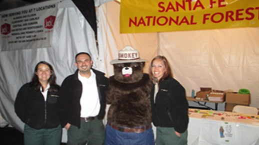 In the predawn hours before the Albuquerque International Balloon Festival, members of the Forest Plan Revision Team pause during their preparations for a photo with Smokey Bear.