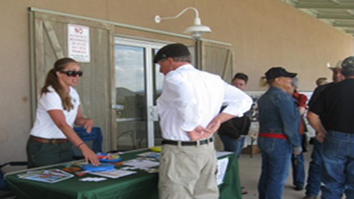 Acting Collaboration Specialist Jessica Richardson talks about Forest Plan Revision with an interested citizen at the Rio Arriba County Fair.