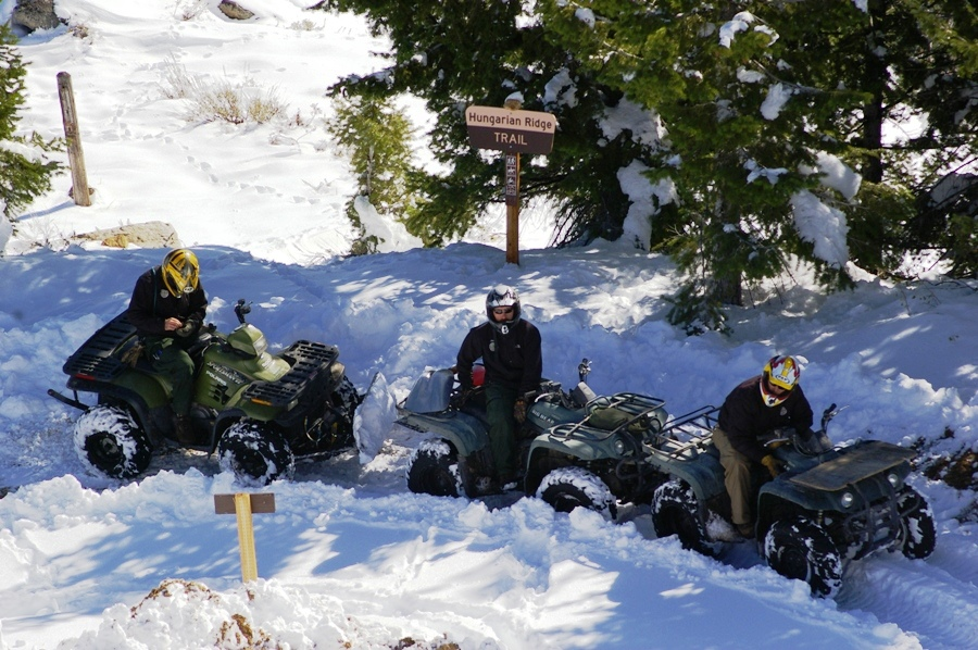 3 Snowmobilers sitting by a trail sign