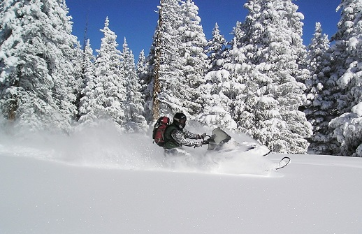 Snowmobile and rider in the deep powder