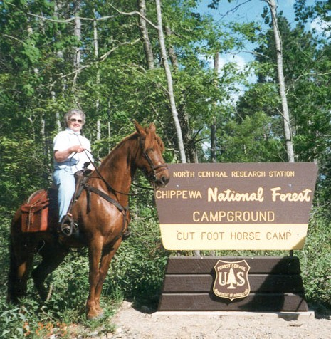 Person riding horse in front of Campground sign
