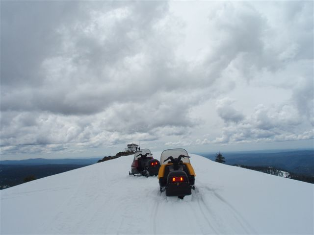 two snowmobiles parked on a snowy ridge