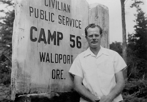 man standing by the wooden sign for Camp 056 at Camp Angell