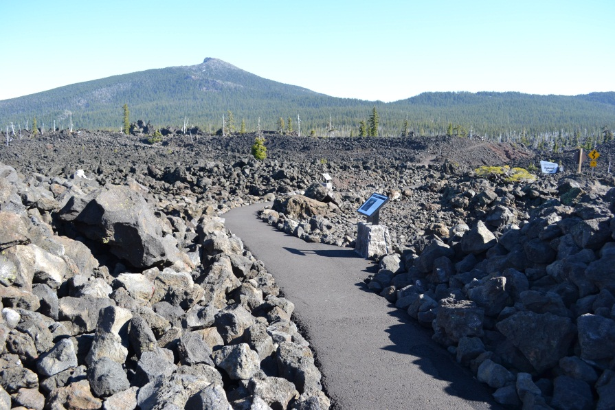 Photo of Lava River Trail showing the asphalt paving surrounded by a field of lava and peak ahead