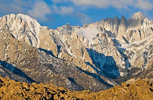 Snow-capped mountains casting shadows in a rocky, rugged wilderness area.