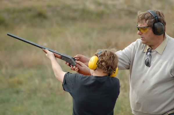 Boy and man demonstrate safe recreational shooting techniques