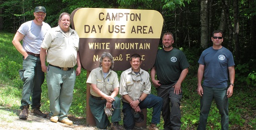 Newly installed sign and proud employees at Campton Day Use Area.