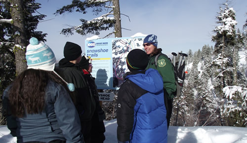 Photo of an employee talking to a group of people about snowshoe trails