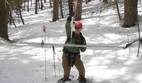 Photo of a man using an instrument to measure the amount of snow pack.