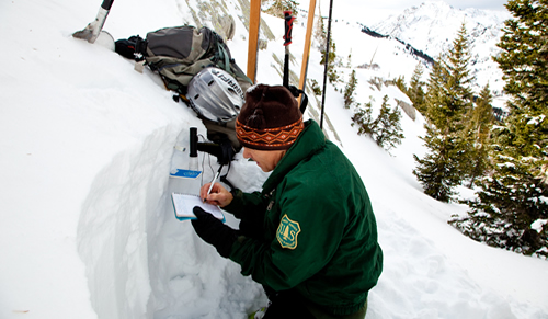 Photo of a man writing some data in a notebook next to a snow bank.