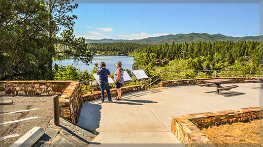 Inquisitive visitors learn about Lynx Lake by reading interpretive signs